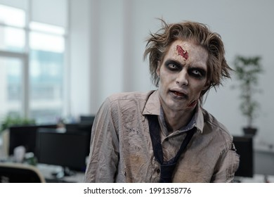 Ugly man with zombie greesepaint on face standing in front of camera