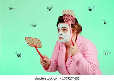ugly overweight woman wearing a pink robe and with a beauty mask and curlers chasing insects with a fly swatter on green studio isolated background