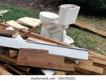 The ugly phase of home renovation featuring old toilet on front lawn.