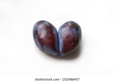 Ugly plum. Spoiled plum in the shape of a heart on a white background. Ugly fruit. Funny food. Spoiled food.