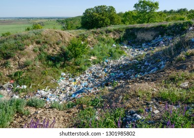 Ugly spontaneous garbage dump in the beautiful nature place near Podgorodnee location in spring sunlight, Dnepropetrovsk region, Ukraine.