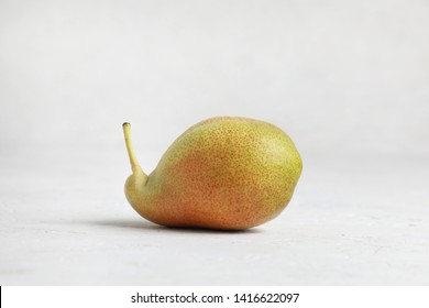 Ugly vegetables , ripe green pear of bizarre shape , on a white background .