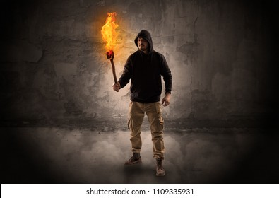 Ugly wayfarer with burning torch in his hand in front of a crumbly wall concept
