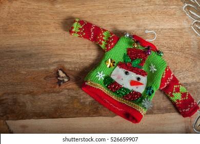 Ugly winter sweater laid on a wooden table background