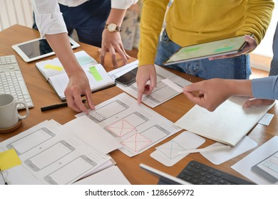 UI creative designer team designing wireframe layout for responsive mobile smartphone application in office