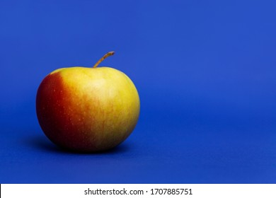 uicy red apple. Bright blue background. Healthy diet and vegan nutrition. Close-up.