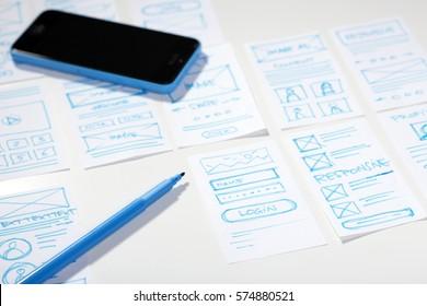 UI/UX designer desk with blue marker, smartphone and sketches for mobile application screens