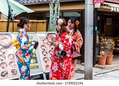 Uji, Japan - April 14, 2019: Traditional village town city with store shops and people tourists wearing kimono costumes young women by restaurant