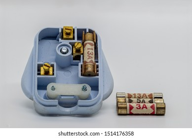 A UK 3 pin plug with 3 different rated fuses 3 Amps 5 Amps and 13 Amps on a white background