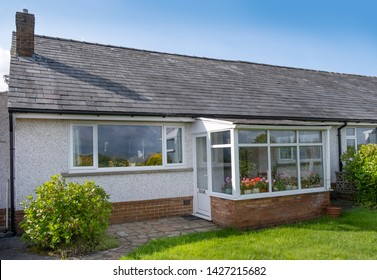 UK 60's bungalow with slate roof, white quartz render and upvc double glazed windows and front porch.
