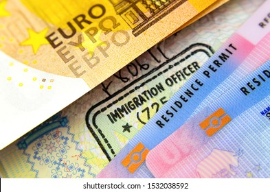 UK Biometrical Residence Permit cards (BRP), immigration stamp in passport and a Euro banknote. The concept photo for immigration between UK - EU.