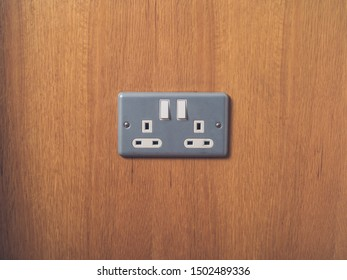 A UK British electrical wall socket on wooden wall