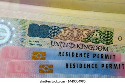 UK BRP (Biometrical Residence Permit) cards for Tier 2 work visa placed on top of UK VISA sticker in the passport. Close up photo.