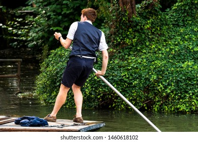 UK, Cambridge - August 2018:  Male student wearing shorts and a waist coat punting on the River Cam