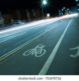 UK cycle lane at night with street lamp and vehicle lights slow exposure