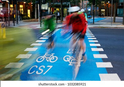 UK cycle lane with white bicycle sign mark at evening, London. Motion Blurred Fast Moving Cyclists Present.