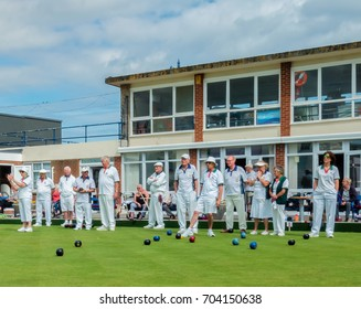 UK, Devon, Teignmouth, August 2017. The quintessentially British game of crown green bowling, showing a competitive match with the Team Captain indicating the jack with his foot.