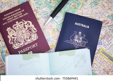 UK EU British passport and Australian passport on a map with a pen and open passport pages