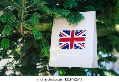 UK flag printed on a Christmas shopping bag. Close up of a shopping bag as a decoration on a Xmas tree on a street in Great Britain. Christmas shopping, local market sale and deals concept.