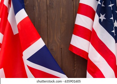 UK flag and USA Flag on wooden brown background.