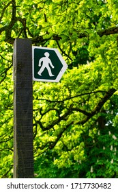 A UK footpath sign on a wooden post, indicated by a white figure on a green background with an arrow head shape.  Green trees and leaves fill the background.