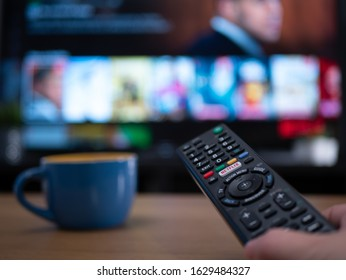 UK, Jan 2020: Netflix remote control with TV behind in evening with Netflix menu