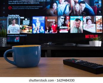 UK, Jan 2020: Netflix trending now menu displayed on television set in home setting with mug