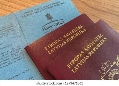UK, LONDON, DECEMBER 2018: Latvian passport and UK registration certificates (concept)