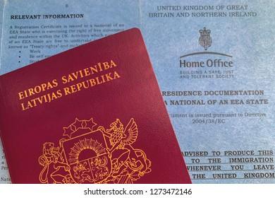 UK, LONDON, DECEMBER 2018: Latvian passport and UK registration certificate (concept)