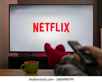 UK, March 2020: TV Television Netflix logo watching with feet up comfy at home