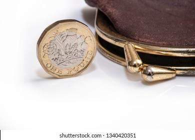 UK money concept, pound coin next to purse