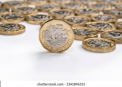 UK money, pound coin standing on edge with coins in background