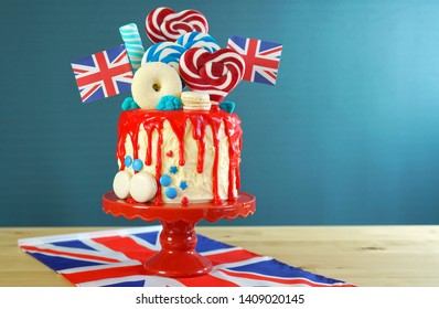 UK on-trend candyland fantasy drip cake with red, white and blue decorations, lollipops and flags with copy space.