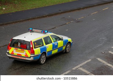 Uk police vehicle on a wet road with the blue lights on