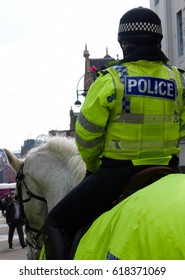 UK police woman on horseback in city center.