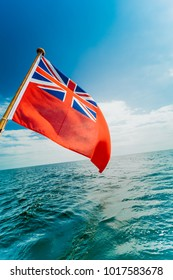 The uk red ensign the british maritime flag flown from yacht sail boat, blue sky and baltic sea. Summer and travel voyage