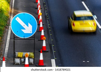 UK Road Services Roadworks Cones and directional Signs on motorway with yellow car passing