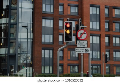 Uk road sign ordering no right turn and advising of bus lane camers, with trafic lights changing colour and a large red building with a glass stair way in background