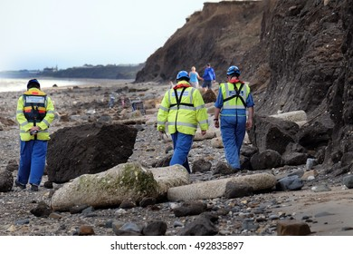 UK. Skipsea, Yorkshire, September 2016. Suspected world war two ordnance being searched for by UK coastguard personnel on holiday beach frequented by families and others. Danger of explosion.