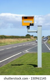 UK static speed camera with speeding cars approaching on a rural road