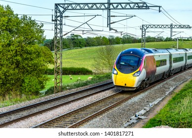uk train railroad next to rapeseed field in bloom day view in england. spring railway landscape