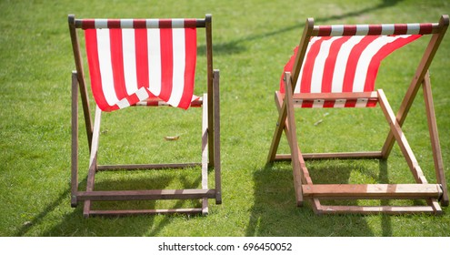 UK two red and white stripe portable deck chairs blowing in wind