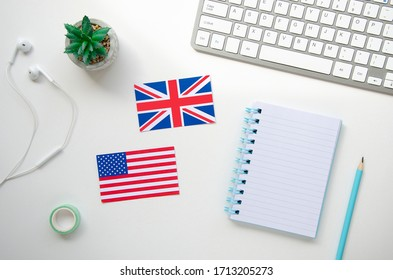 UK and USA flags on a white school desk with keyboard and earphones. Top view Learn a foreign language at home concept