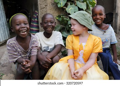 UKEREWE - TANZANIA - JULY 2, 2015: Unidentified albino child and boys on July 2, 2015 in Ukerewe, Tanzania. Many traditional healers have been arrested recently in Tanzania because of albino murders