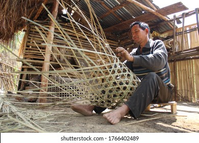 Ukhrul, Manipur/India - 5 April 2020 : A middle aged man weaving traditional bamboo basket in his country work station