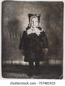 UKRAINE - APRIL, 14 1942: Vintage photograph of a little 4 years old girl dressed in a winter fur coat, mittens. felt boots and hat. Old Studio photo