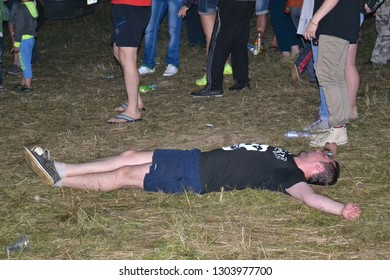 UKRAINE, Belokopytovo - July 7, 2014: Drunk man lies on the ground in nature at a rock concert at the moto meeting Northern Lands, the theme of alcoholism and wrong lifestyle