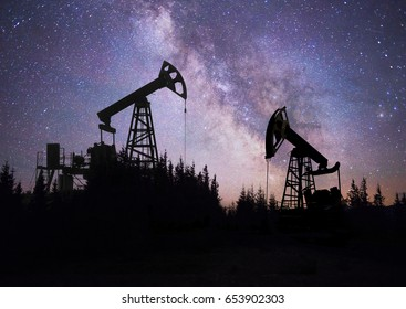 Ukraine, Carpathians night photo of the European oil rig rocking the pump on the background of the Milky Way Galaxy in the universe. Symbol of energy and ecology of planet Earth