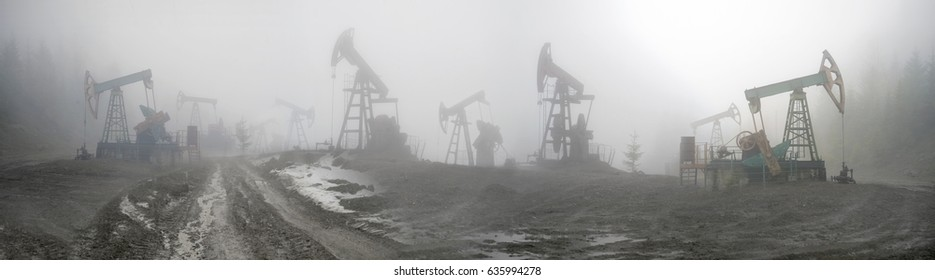 Ukraine, Carpathians old ancient classical Romanian and Soviet oil pumps rocking at dawn amid the damaged ecology of alpine meadows work to produce the energy of the modern world
