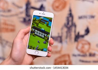 Ukraine. Cherkassy - 15 may 2019 year. Close up of man hand playing Crossy Road on smartphone